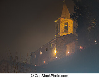 Church on a hill, by night, in fog.