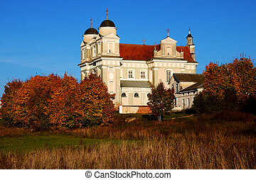 Church on the background of blue sky and beautiful golden trees in autumn, background