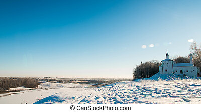 Church on the hill in background of a winter landscape