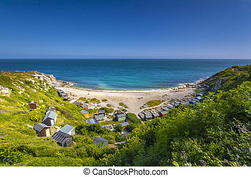 Tucked away on the east coast of the Isle of Portland is a tiny cove with multi-coloured beach huts and white pebbles