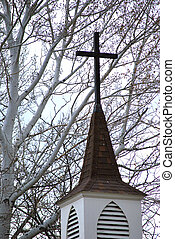 Looking up at a church steeple and cross.