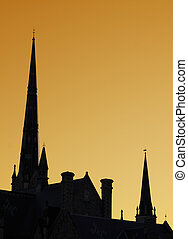 The spires of a cathedral against an orange sky.