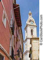 Church tower and red house in the center of Xativa