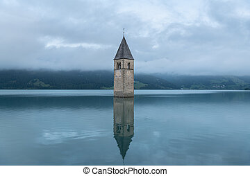 Church tower of Altgraun, Reschensee on a cloudy morning in summer