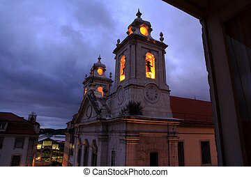 Church with glowing bell tower at night