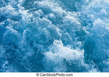 Churning blue water in the ocean shows lots of turbulance and splash. Good for background image.