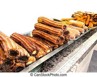churros, ligado, um, tenda mercado, em, um, panificadora, shop., doce, famosos, espanhol, sobremesa, com, molho chocolate, cima