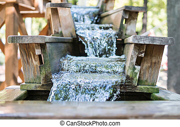 Chute with running water - Fast stream flowing on a wooden...