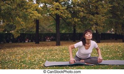 ciało, praktyka, yoga mata, natura, kręgosłup, concept., posiedzenie, ruchomy, młody, wstecz, zdrowy, osobnik, zdrowie, podczas, wykonuje, elastyczny, dama, park.