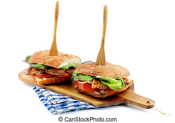 Ciabatta Sandwiches with Bacon, Tomato, Lettuce and Sauces on Cutting Board Arranged with Wooden Fork isolated on white background