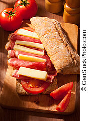 ciabatta sandwich with ham, cheese, tomato on wooden board