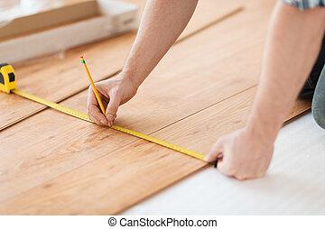 cicatrizarse, de, manos masculinas, medición, madera, embaldosado