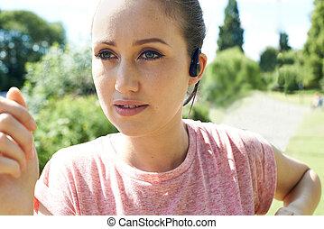 cicatrizarse, de, mujer joven, corriente, en el estacionamiento, escuchar música