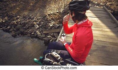 ciclista, ponte, mulher, fone ouvido, caso, sacolas, capacete, sobre, abertura, descansar, river., desportista, luminoso, livre, inserção, branca, orelha, caucasiano, sportswear