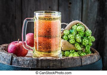 Cider beer with ingredients on old barrel