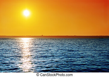 cielo anaranjado, en, ocaso, encima, agua azul