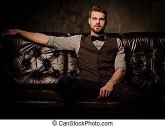 ciemny, brodaty, młody, posiedzenie, człowiek, przystojny, wygodny, staromodny, sofa, skóra, tło.