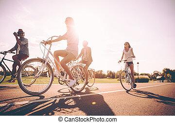 cieszący się, kąt, ludzie, razem., młody, beztroski, patrząc, bicycles, niski, jeżdżenie, wzdłuż, szczęśliwy, dzień, droga, prospekt