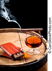 Cigar and cognac on black background with old barrel