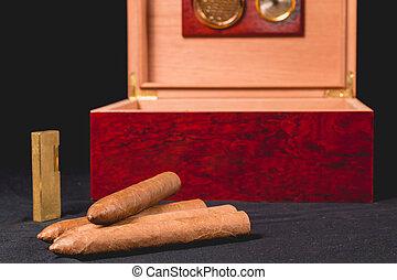 Cigar box on black background and lighter