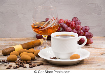 Cigar, brandy, cup coffee espresso with chocolate eggs and grape