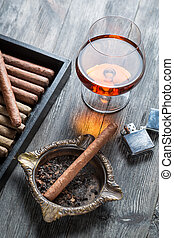 Cigar in ashtray, lighter and cognac