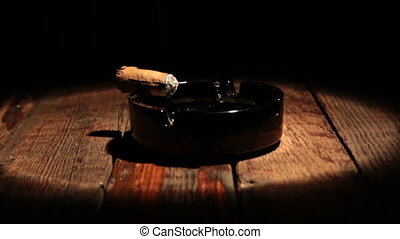 Cigar is lying in an ashtray on a wooden table. Illuminated by the spotlight. Panorama
