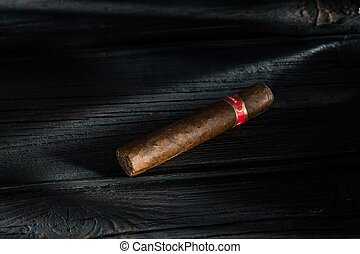 Cigar on old wooden table with blurred background