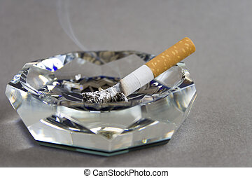 Cigarette and ashtray isolated on grey