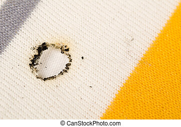 Cigarette burn in the cotton fabric of a shirt