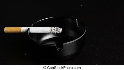 cigarette burning in ashtray time lapse on black wood table