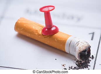 Cigarette butt on calendar. Time to quit smoking concept