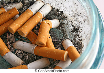 Cigarette butts in a glass ashtray.