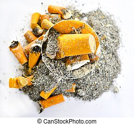 cigarette butts top view on yellow background with magnifier