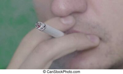 Cigarette in the mouth of a smoker. Close-up. Slow motion. Stock video footage HD / 1920-1080 / MOV / Codec H.264 / 25 fps.
