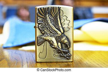 A cigarette lighter with eagle carved on its side