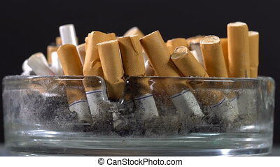 Cigarette stubs in the ashtray rotate on the table