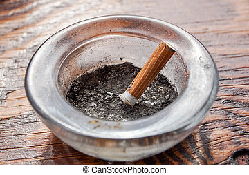 cigarette with ashtray on wood table .