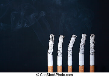 Five cigarettes with smoke and ashes on dark background