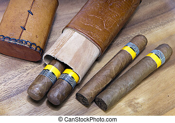cigars twisted from tobacco leaf and a cigar box made of wood in leather for two cigars