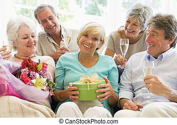 cinco, amigos, con, champaña, y, regalos, en, sala, sonriente