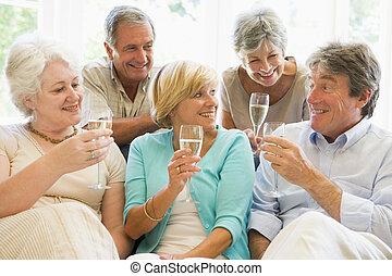 cinco, amigos, en, sala, bebida, champaña, y, sonriente