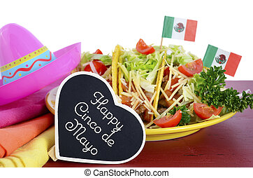 Happy Cinco de Mayo bright colorful party food with platter of tacos on red wood table.