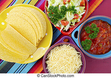 Happy Cinco de Mayo bright colorful party with ingredients for assembling tacos on festive red wood table.