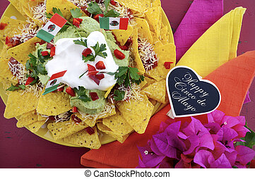 Happy Cinco de Mayo party table with nachos food platter and bright orange, red, and pink napkins on a red wood background.
