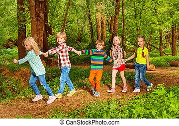 cinco, feliz, niños, ambulante, en, bosque, manos de valor en cartera