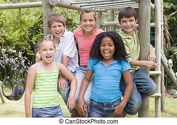 cinco, joven, amigos, en, un, patio de recreo, sonriente