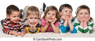 cinco, niños, acostado, alfombra