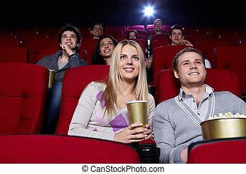 Attractive people are watching a movie at the cinema