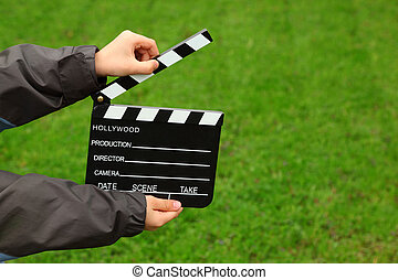 Cinema clapper board in hands of boy in jacket on field with green grass